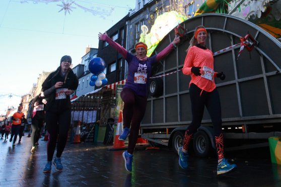 Runners in the MoRun pass through Perth High Street on Sunday.