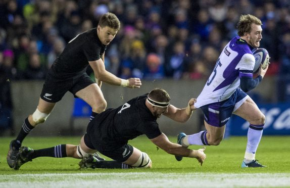 Stuart Hogg is caught by Luke Romano as he tries to go through for Scotland.