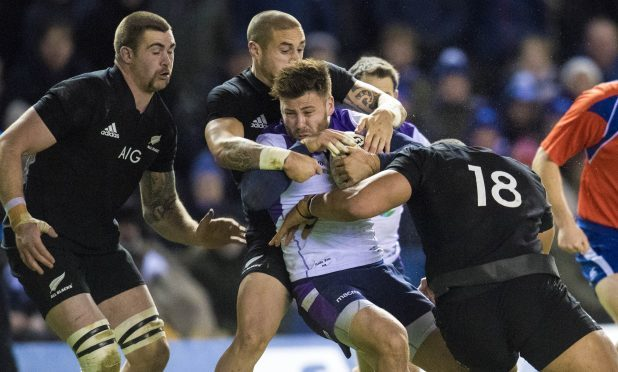 """""""Little guy"""" Ali Price battles through three All Blacks during the game at Murrayfield."""