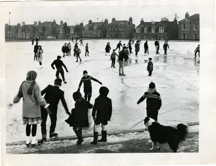 Photograph showing large numbers of people, young and old, having fun with a day of ice skating at Stobsmuir Pond,  December 28, 1962.