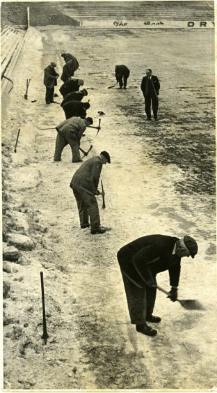 Manager Jerry Kerr watches on as groundsman take picks and shovels to the frozen pitch at Tannadice Park, Dundee. January 1963.