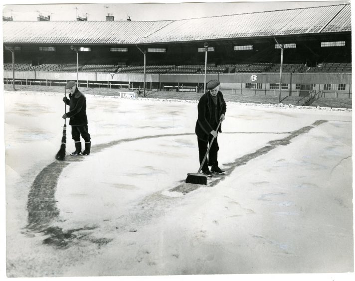 Dens Park in Snow. Photograph showing two men sweeping snow in Dens Park, Dundee, January 17, 1963.