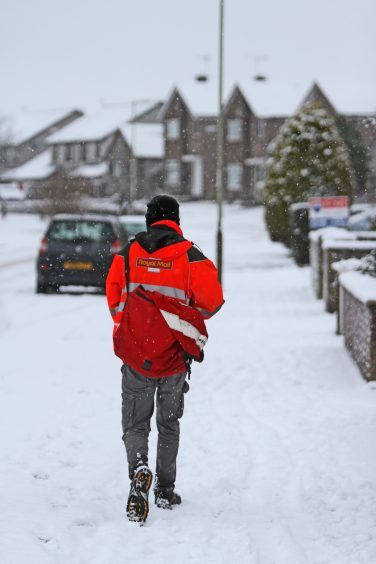 A postal worker continuing with rounds despite several inches of snow in Kinross.