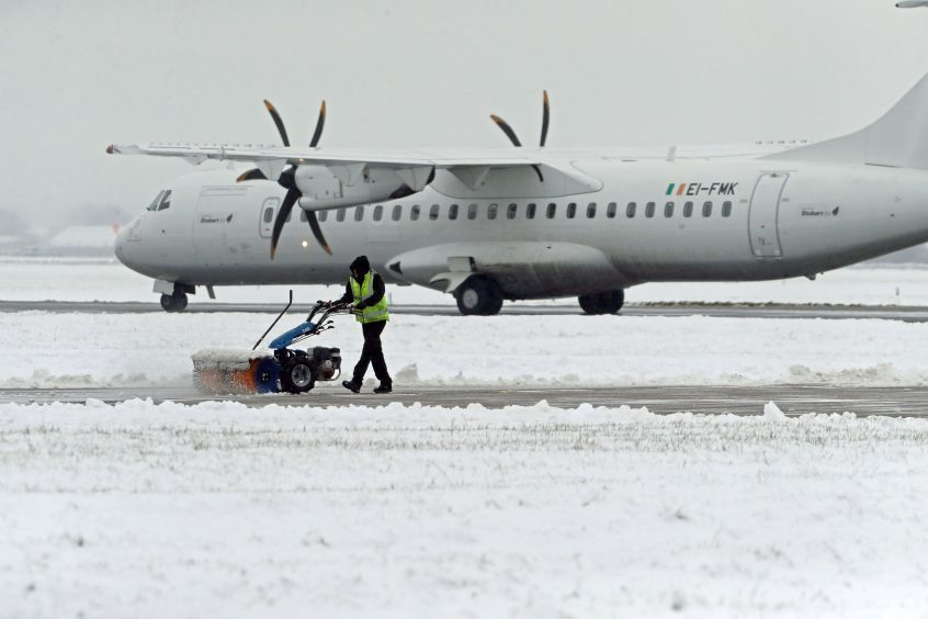 The runway and grounds at Glasgow Airport being cleared of snow as Britain saw one of the coldest nights of the year.