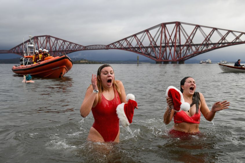 New Year swimmers, many in costume, in front of the Forth Rail Bridge during the annual Loony Dook Swim in the River Forth on January 1, 2018 in South Queensferry, Scotland.