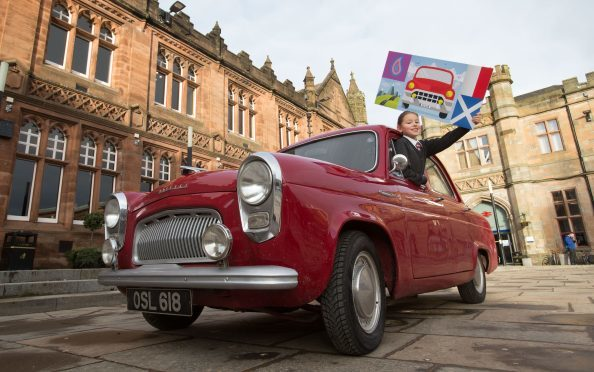 Emilia Kozlowska, 10, who won a competition to design the event start flag, pictured in the Ford Prefect of  Angus crew David Tindal, Alan Falconer and Stephen Woods