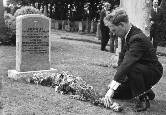 """Ian Robertson placing flowers at the grave of the """"unknown bairn"""" of Tayport."""