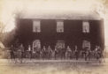 View of group of fifteen men with bicycles outside an ivy-clad house, possibly in the Stanley area.