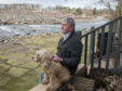 Mike Paton and his dog at his the riverside area, which he has been ordered to rip up.