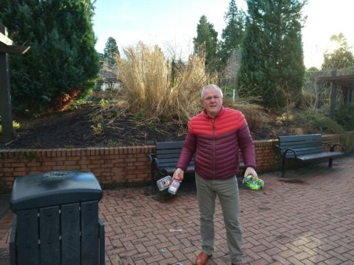 Councillor Peter Barret helps clear up some of alcohol bottles left discarded after another night of underage drinking.