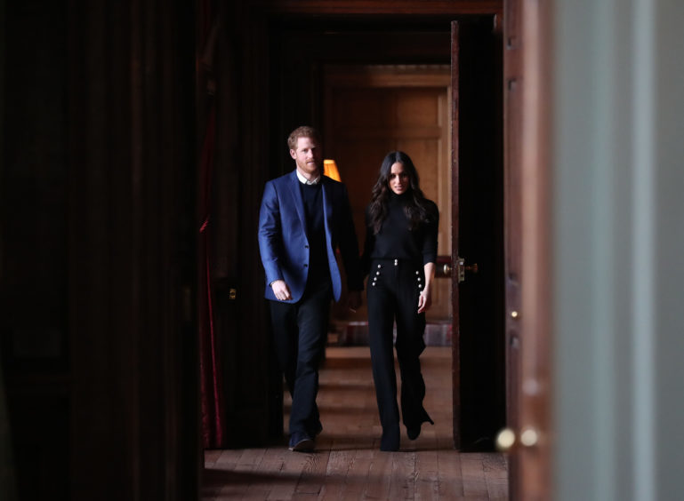 Prince Harry and Meghan Markle walk through the corridors of the Palace of Holyroodhouse on their way to a reception for young people