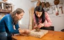Willow weaver Rachel Bower helps Gayle to make a simple bird feeder.