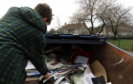 A volunteer sifts through a skip filled with recyclable materials at the old school campus