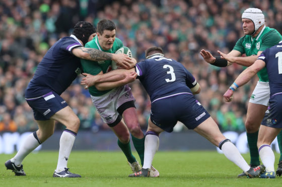 Johnny Sexton is tackled by Gordon Reid and Simon Berghan during Saturday's game in Dublin.