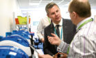 Cabinet Secretary for Finance Derek Mackay talks to a staff member during a ministerial visit to Journeycall in Arbroath.