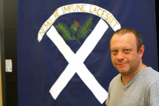 Alex Robbie, from Kirriemuir, beside the Ogilvy Clan flag at the McManus Galleries in Dundee. DC Thomson.