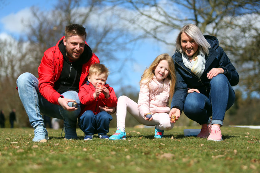 Scott, Connor and Layla Ferrier with Dee Chard rolling their Easter eggs at Camperdown Park.