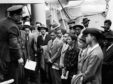 "Jamaican immigrants with RAF officials from the Colonial Office after the ex-troopship HMT ""Empire Windrush"" landed them at Tilbury in Essex in 1948."