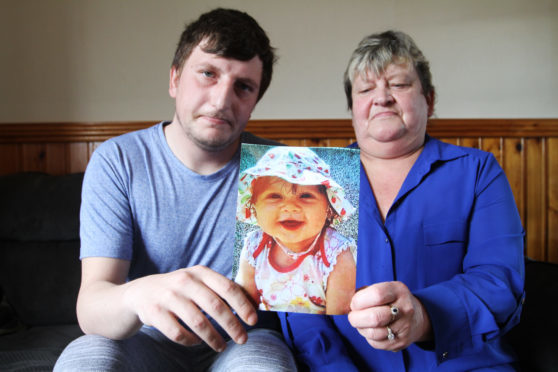 Madison's dad Thomas Haldane and gran Alexis Munro with a photo of the murdered toddler.
