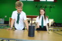 David Bachanek, P4, and Caitlin Walsh, P6, with the 'Alexa' which enables them to find out what is on the school dinners menu, at Rowantree Primary School.