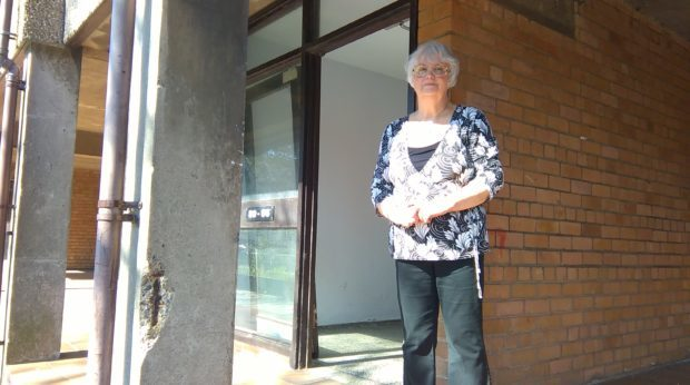 Cecelia Proctor stands beside a broken door and an eroded pillar at the Nicol Street flats complex.