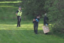 Forensic officers investigate the scene at Caird Park Golf Club.