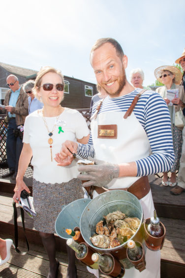 Hazel Peplinski (Racecourse chief executive) trying oysters from 'The Oysterman' Ferras Seguer.
