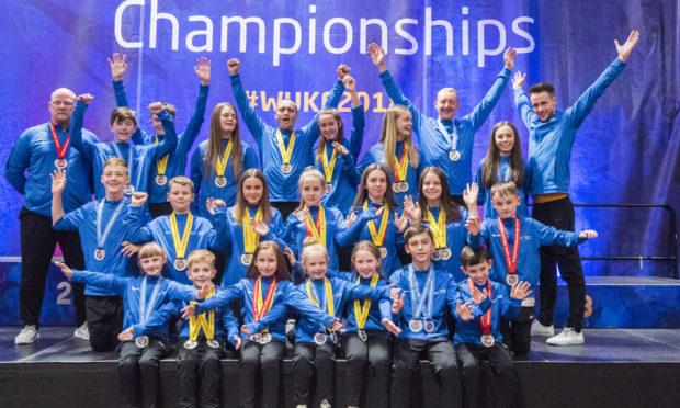 All medal winners from Team Kanzen Karate Scotland with coach Dan Woods.