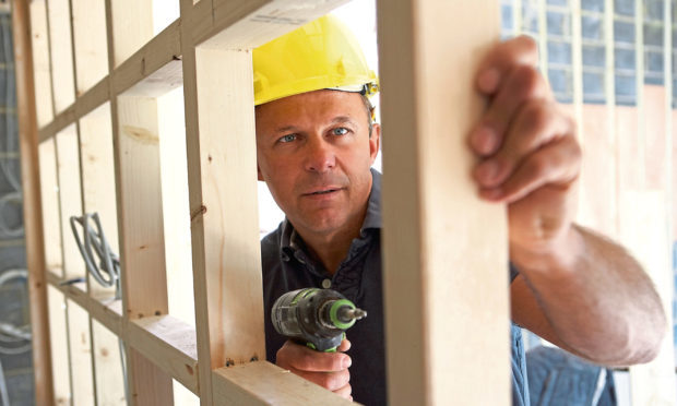 A construction contractor builds up a timber partition