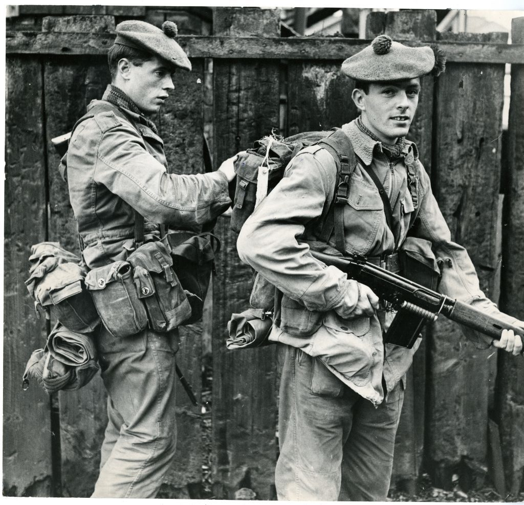 Black Watch at Ulster. Photograph showing R. Rushford, from Cowdenbeath, lending T. Grant, from Dundee, a hand with his kit as the Black Watch are sent to Ulster. June 30 1970.