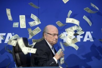Then FIFA president Sepp Blatter has banknotes thrown at him by British comedian Simon Brodkin in July 2015 (pic: Ennio Leanza/Keystone via AP).