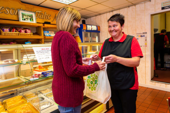 Sandra Reid of Dave's Diner serves local resident Ann Murray with the new compostable carrier bag.