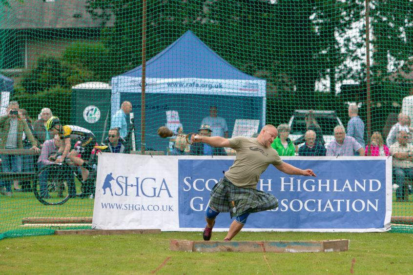 Strong men compete throwing the 28Kg Hammer