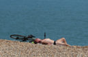 A man relaxes in the sunshine on the beach during the 2018 heatwave.