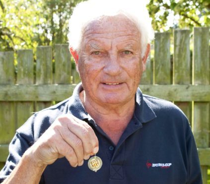 Mr Robb with a medal from his glittering career.