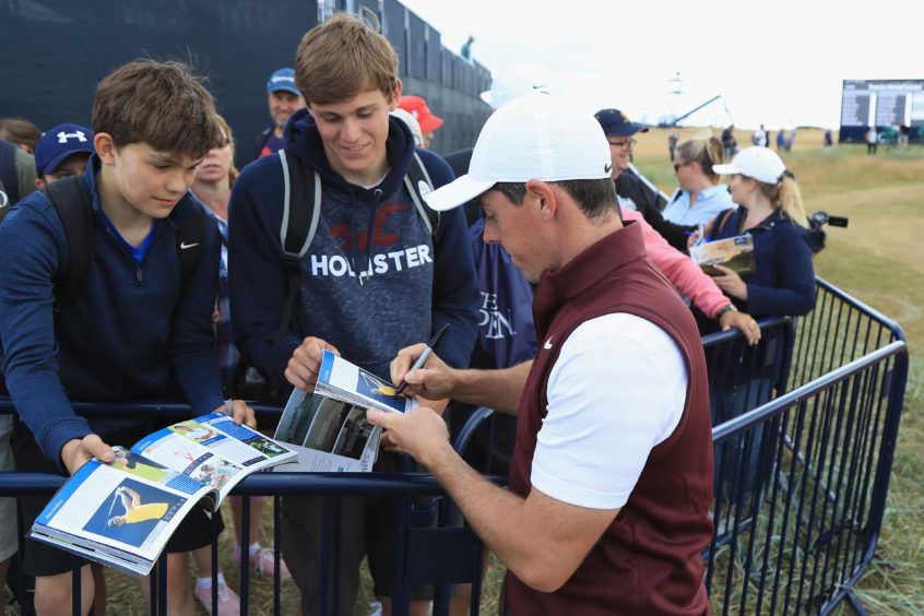 Rory McIlroy of Northern Ireland signs autographs for fans.