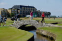 Tom Watson, Bernhard Langer and Miguel Angel Jimenez cross the Swilcan Bridge during the Senior Open.