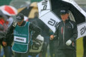 Miguel Angel Jimenez shelters from the rain during the final round of the Senior Open.