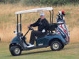 US President Donald Trump drives a golf buggy on his golf course at the Trump Turnberry resort in South Ayrshire.