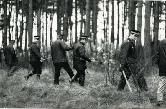 Police search woodland in Fife during the search for Mrs Hunter.