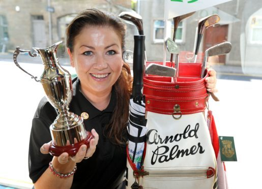 Karina MacKinnon, manager of the Golf Shop of St Andrews, with Arnold Palmer's golf bag which is on display in the shop window for the duration of the Senior Open
