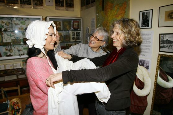 Gayle Ritchie tries on some vintage children's clothes at Glenesk Folk Museum with help from Virginia Aspinwall and Maria MacDonnell.