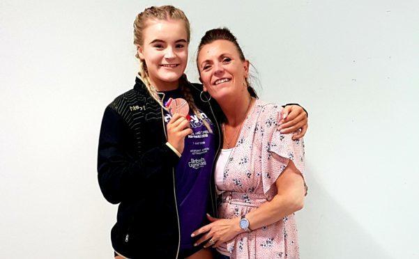 Tegan Gaffrey showing off her medal, accompanied by her mum, Cordelia.