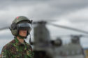 A serviceman stands in front of a Chinook helicopter at Leuchars Station in July 2018.