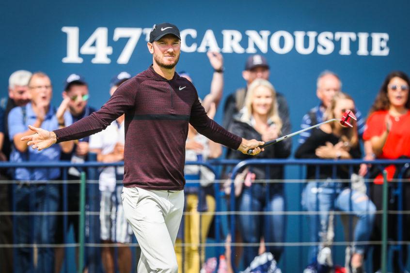 Chris Wood celebrating holing a putt.