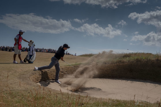 Rory McIlroy comes out of a bunker on his way to a two-under 69 on the opening day at Carnoustie.