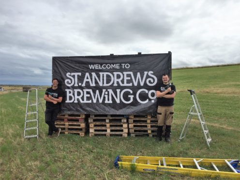 Head brewer Rob Lowe and sales and marketing manager Ben Wallace pose by one of their new billboards.