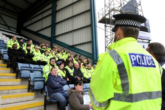 Stewards are briefed by police ahead of a match at Dens Park.