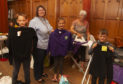 The Rev Maggie Hunt with Ann Menmuir hard at work ironing all the clothes with Alysha Torrie(10) and her brothers Liam(12)(left) and Aidan(12).