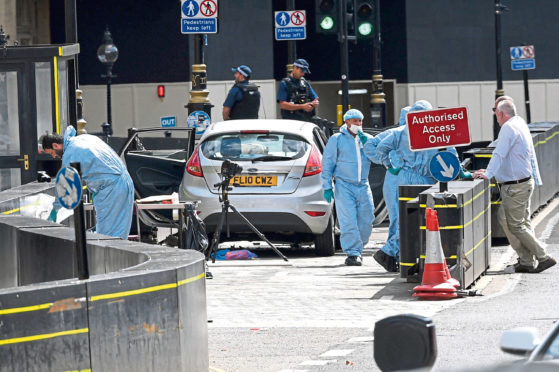 Forensic officers by the car that crashed into security barriers outside the Houses of Parliament.